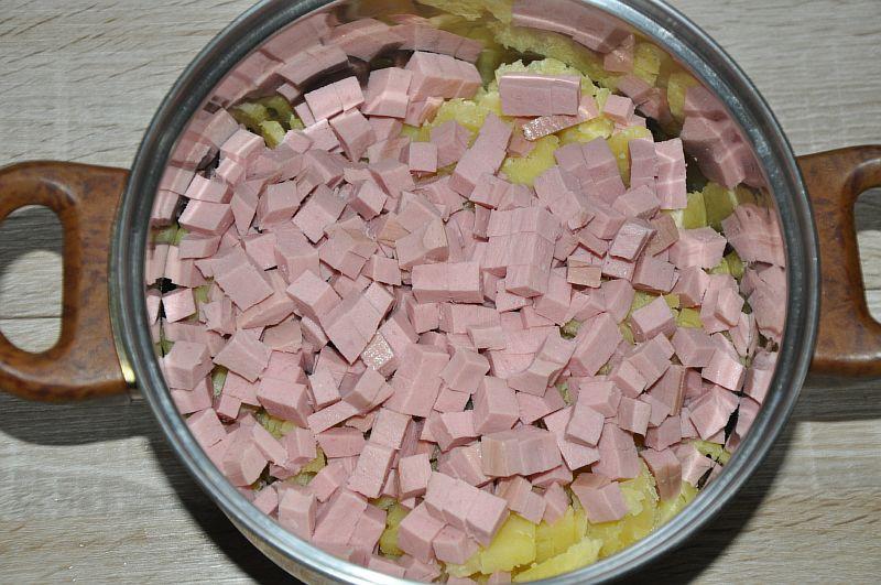 Отправляем в кастрю нарезанную колбасу